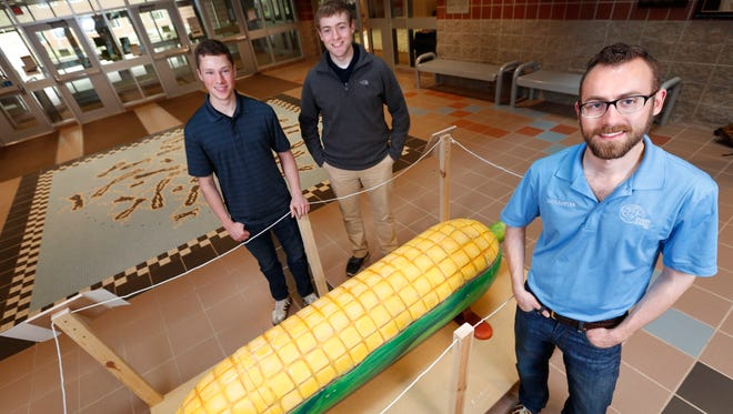 Iowa State Engineers Without Borders members, from right, Joe Gettemy, Jason Schmitt and Kevin Strohm auctioned off a folk-art coffin shaped like an ear of corn to help fund an earthen dam project in the artist's native Ghana.