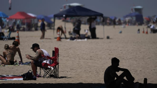A man sits in the shade underneath a pier in Huntington Beach, Calif., Saturday, Sept. 5, 2020. California is sweltering under a dangerous heat wave Labor Day weekend that was spreading triple-digit temperatures over much of the state, raising concerns about power outages and the spread of the coronavirus as throngs of people packed beaches and mountains for relief.