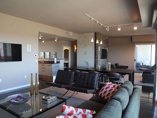 The condo has wood and tile flooring and exposed concrete walls.