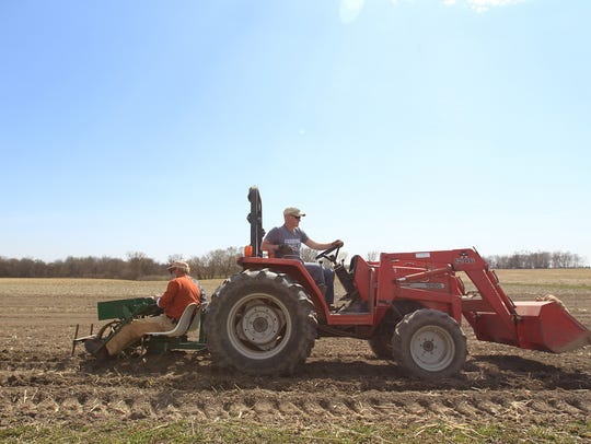 Jason Grimm drives a tractor as John Boller and Scott