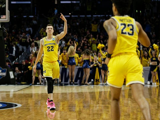 Michigan guard Duncan Robinson (22)  celebrates a 3-point basketball made by guard Ibi Watson (23), right, during the first half of Sweet 16 of the NCAA tournament in Los Angeles on Thursday, March 22, 2018.