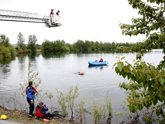 The Salem Fire Water Rescue team and the Albany Fire and Linn County Sheriff's Office Dive Team search for a man who was spotted swimming in Mission Lake in Salem on Wednesday evening, but disappeared under the water. Photographed on Thursday, May 31, 2018.