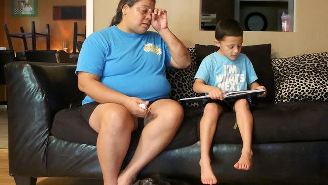 Andrea Melendez, left, wipes her eyes, while her 6-year-old grandson Kysun looks at a book, as she talks about the wreck that killed Kysun's mother.