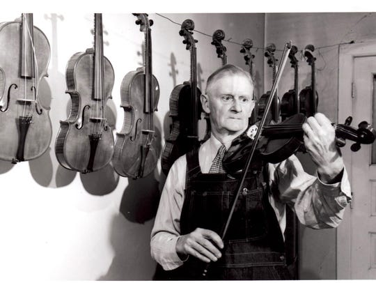 Mr. Al Smith with the violin he crafted for President