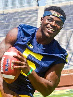 Michigan defensive back Jabrill Peppers (5) laughs as he pose for photographers on the field in Michigan Stadium during the NCAA college football team's annual media day in Ann Arbor, Mich., Thursday, Aug. 6, 2015.
