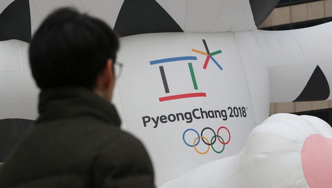 A man walks by an official emblem of the 2018 Pyeongchang Olympic Winter Games, in downtown Seoul, South Korea, Friday, Dec. 29, 2017.