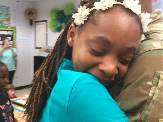 Alaysia, 12, hugs her big brother, Anthony Foster, who she hasn't seen in  about eight months. Anthony has been deployed overseas and made a surprise visit home.