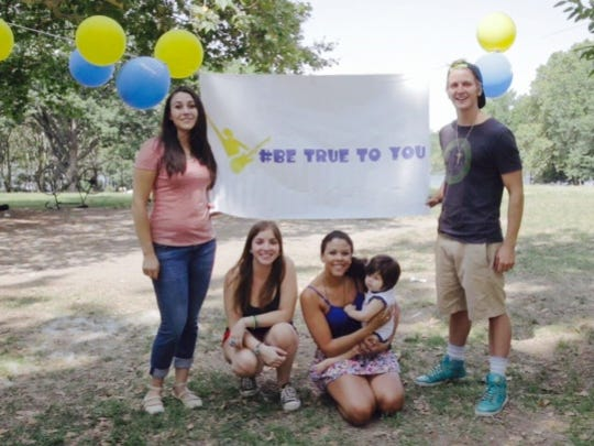 Ashley Tobias poses with friends holding a banner for her Be True to You program.