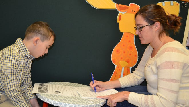 Cindy Feirstine helps first grader Austin Murray with his work.