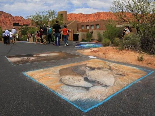 The red cliffs behind Coyote Gulch Art Village glow Sunday afternoon during the Kayenta Street Painting Festival in Ivins City.
