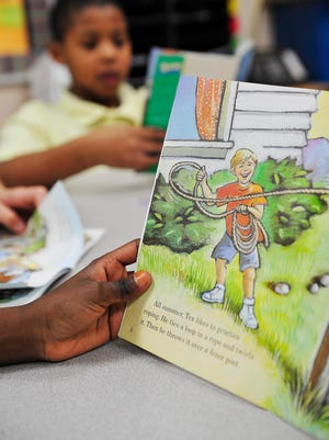 """Prisca Shaibu, 9, reads the book """"Ready for the Rodeo"""" in reading teacher Brenda Pollock's class at A.Z. Kelley Elementary School."""