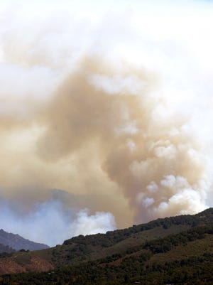 As photographed from Laureles Grade Road, smoke from both controlled burns and the Soberanes Fire billows high in the mountains behind E. Carmel Valley Road on Sunday, August 7th, 2016.