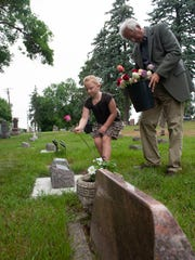 Jenna Jensen, along with Gary Conradi place flowers on the new grave markers Tuesday at Woodlawn Cemetary. Jensen has made headlines recently due to her passion for remembering lost infants.