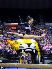 Five-time All-American Rheagan Courville completes a jump on the balance beam during a recent gymnastics competition.