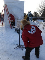 Snow sculptors, from left, Michael Sponholtz, Milwaukee, Mike Martino, La Crosse, and Tom Queoff, Milwaukee, work on the tree frog sculpture in 2013 at the Woodson Museum in Wausau.