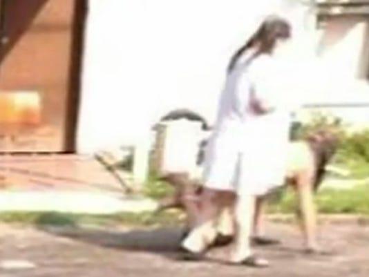 Woman walks naked man
