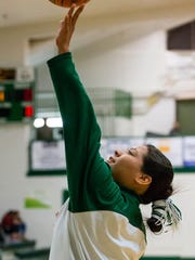 In this Feb. 2, 2016, photo provided by Richard Johnson, Mikaila Kayanni-Lee, a member of the girls basketball team at Flagstaff, Ariz., High School, practices her jump shot with her hair tied back in a traditional Navajo bun during pre-game warmups. But before play could begin the referee made her and other team members remove the hair ties, saying they were a safety hazard. This sparked sharp criticism from the school's principal and the president of the Navajo Nation. Officials say the hair ties won't be prohibited in the future.