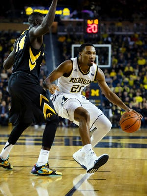 Michigan Wolverines guard Zak Irvin (21) is defended by Iowa Hawkeyes guard Peter Jok (14) in the first half at Crisler Center.