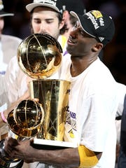 LOS ANGELES, CA - JUNE 17:  Kobe Bryant #24 of the Los Angeles Lakers struggles to hold both the Larry O'Brien trophy and the MVP trophy after the Lakers defeated the Boston Celtics in Game Seven of the 2010 NBA Finals at Staples Center on June 17, 2010 in Los Angeles, California.  NOTE TO USER: User expressly acknowledges and agrees that, by downloading and/or using this Photograph, user is consenting to the terms and conditions of the Getty Images License Agreement.  (Photo by Christian Petersen/Getty Images)