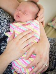 Jake and Amy Niederhauser hold their newborn baby girl