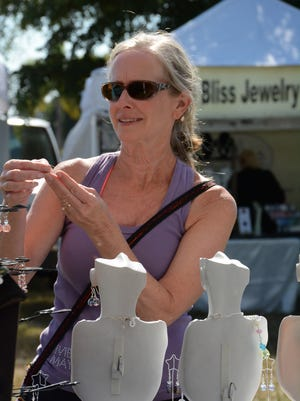 Julie Bisbey inspects the jewelry at Katherine's Bead Design. The Marco Island Farmers' Market opened its 2016-17 season Wednesday morning at Veterans' Community Park.