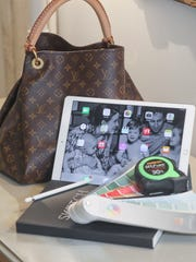 A Louis Vuitton bag with an ipad pro and work tools.