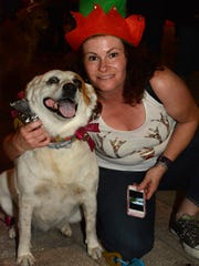 Lori Hardacker from Massachusetts with Essie, her Tennessee mutt. The Christmas Island Style Canine Christmas Parade filled the Esplanade with dolled up dogs on Tuesday evening.