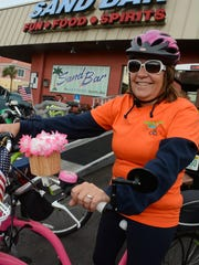 Patty Broad decorates her handlebars with flowers. The Tour de Taverns bicycle poker run Saturday raised funds to help cancer patient Lisa Mayfield, a longtime supporter of the event.