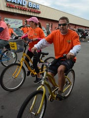 Beth Savary heads out with Steve Demings. The Tour de Taverns bicycle poker run Saturday raised funds to help cancer patient Lisa Mayfield, a longtime supporter of the event.
