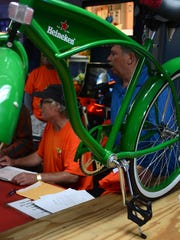 Organizer Jim Boylan, seated, signs up last-minute entrants. The Tour de Taverns bicycle poker run Saturday raised funds to help cancer patient Lisa Mayfield, a longtime supporter of the event.