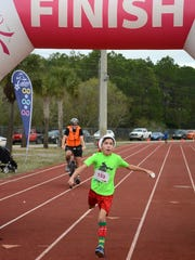 Riley Hart, 12, is the first to cross the finish line.