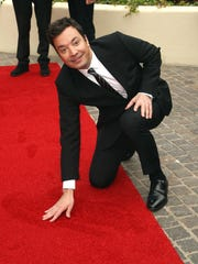 Jimmy Fallon helps unroll the Golden Globes red carpet.