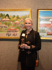"""Artist Betsy Ross Koller with some of her work. The Marco Island Center for the Arts held a reception Tuesday evening for an exhibit of paintings by Koller, showcasing her """"naive"""" interpretations of rustic scenes, many of them snowscapes, at their gallery on Winterberry Drive."""