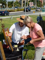 "Artist Pat Perrotti, left, discusses her work with Dot Hollenbach. The Marco Island Foundation for the Arts held a ""Brushes and Paint"" art show Saturday at Marco Lutheran Church's parking lot."