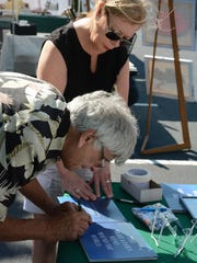 "Gene Mandarino signs one of his books for Ann Marie Zarba. The Marco Island Foundation for the Arts held a ""Brushes and Paint"" art show Saturday at Marco Lutheran Church's parking lot."