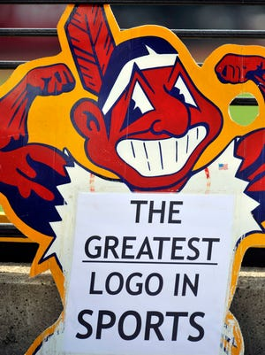 An fan holds up sign of Chief Wahoo.