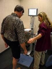 Alan Bell of Marco Island steps onto a BioSway testing device, helped by a physical therapist named Kathleen. The NCH Marco Healthcare Center hosted an event on Wednesday focusing on how to prevent falls, at their facility on Bald Eagle Drive opposite City Hall.