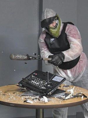 Katarina Struck breaks a laptop computer with a baseball bat. The Rage Room opened Saturday, Feb. 18, 2017, at 520 W 15th Ave., Oshkosh.