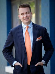 Brett Howard, owner of the men's clothing store Evolve, shows of a classic option for men's derby fashion. He is wearing a navy striped suit with a floral blue gingham dress shirt, coral tie and pocket square to match. April 5, 2015