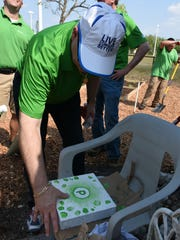 Steve Campbell of Publix adds his thumbprint to a paver that will be incorporated into the project.