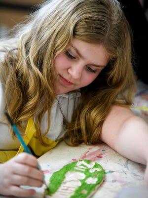 Cassie Condor paints a garden plaque as children make garden art to be sold at Patchwork Central's pancake breakfast fundraiser this weekend.