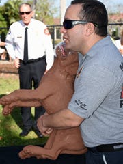 Firefighter/paramedic Heath Nagel shows how to perform the equvalent of the Heimlich maneuver on a larger pet. Monday morning, the Marco Island Fire-Rescue Dept. launched their Emergency Pet Care program, and demonstrated canine CPR, in a presentation at the Mackle dog park.