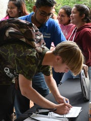"""A student signs a """"no texting"""" pledge after completing the course."""