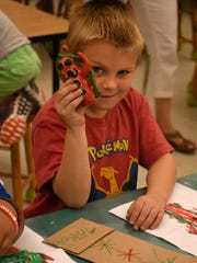 Jacob's outfit matches his clay and paper monster. Kindergarden students at Pelican Marsh Elementary School had their drawings of monsters rendered in three-dimensional clay by ceramics students at Barron Collier High School, in a cooperative learning initiative between the two schools.