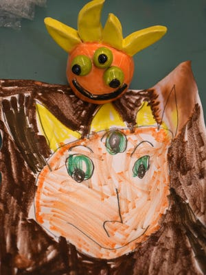 A clay monster looks down at his paper inspiration, with one of three eyes. Kindergarden students at Pelican Marsh Elementary School had their drawings of monsters rendered in three-dimensional clay by ceramics students at Barron Collier High School, in a cooperative learning initiative between the two schools.