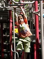 Colin Gilgenback, 5, of Fond du Lac, climbs on a piece of BCI Burke playground equipment at Lakeside Park.