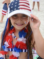 Gigi Politi, 7, is a walking flag. Marco Island celebrated Independence Day at the beach on July 4th, with beach games, fireworks, and a variety of weather.