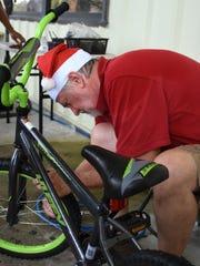 Bikes for Tykes volunteer Scott McGaughey adjusts a