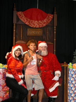 """Davion Grant, 12, poses with Santa and Mrs. Claus as he collects his backpack. Nine area Kiwanis clubs joined together with an array of community organizations and sponsors to provide """"Christmas in July"""" for over 900 underprivileged kids, handing out backpacks, bicycles and more  on July 29 at the Florida Sports Park."""