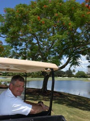 The royal poinciana tree behind general manager Peter
